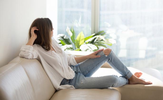 uma mulher está no sofá olhando em direção a janela