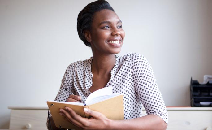 uma mulher sorri enquanto escreve em um caderno.