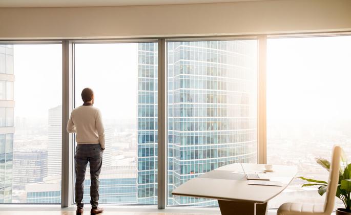 homem olhando para a janela de um prédio