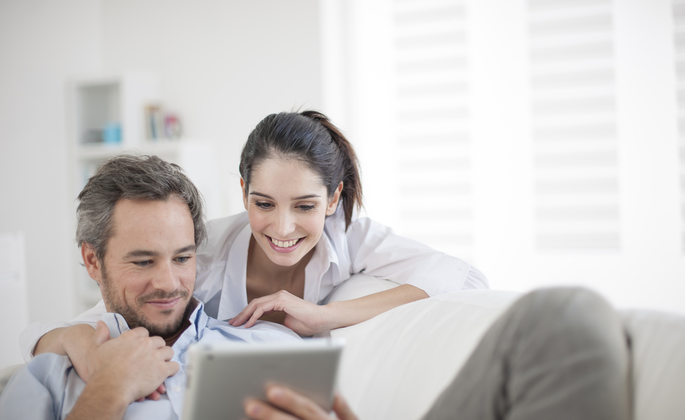 casal sorri ao olhar em um tablet