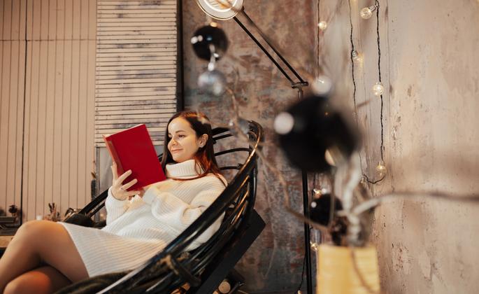mulher lendo um livro em uma sala de estar