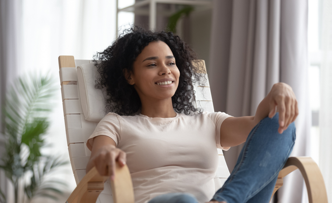 mulher sentada em uma poltrona, sorrindo