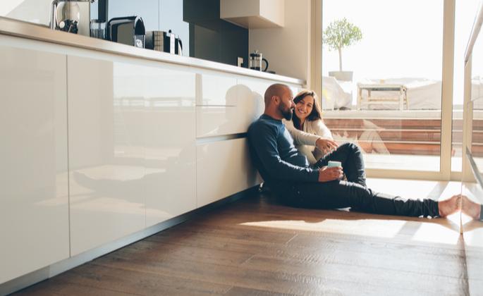 casal sentado no chão da cozinha de apartamento - CIMA