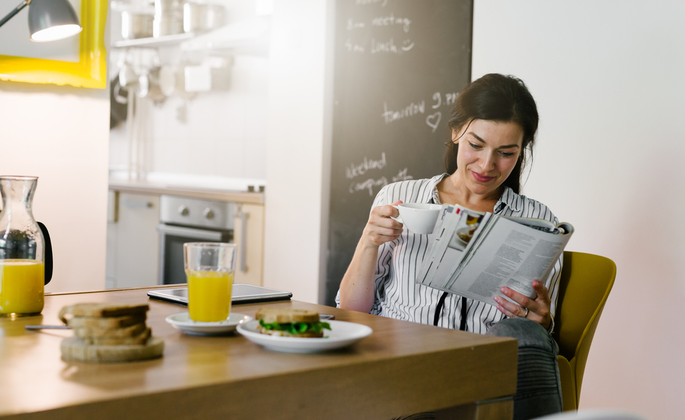 mulher tomando café e se informando pela manhã