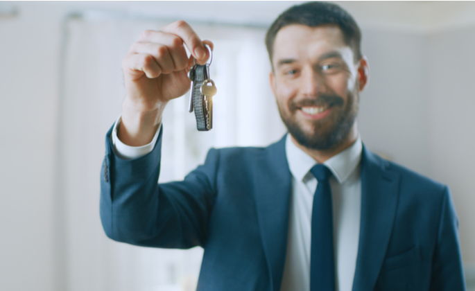 homem sorrindo segurando chave de imóvel - CIMA