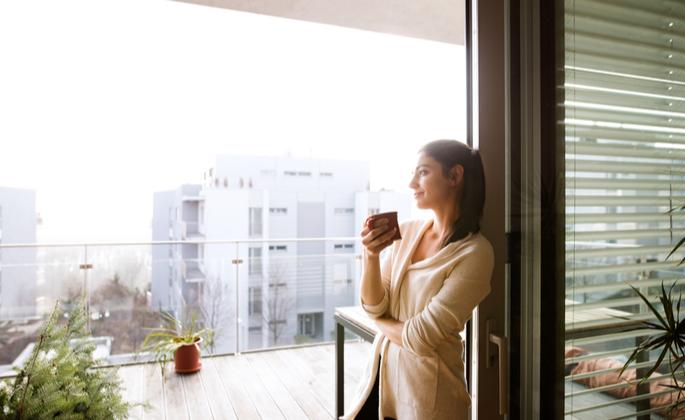 Mulher admirando vista de seu apartamento seguro - CIMA