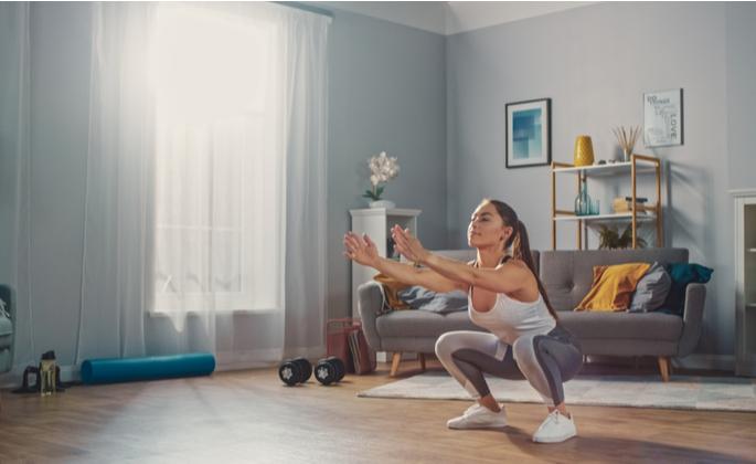 Mulher praticando exercício físico em casa