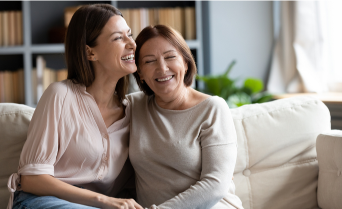Duas mulheres sentadas no sofá sorrindo