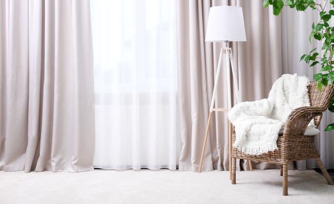 ambiente bem iluminado com cortinas e poltrona